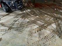 Pista del neumático de la carretilla elevadora en la tierra sucia foto de archivo