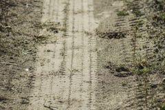Pista del neumático y del enganche en un camino de tierra de lado a lado foto de archivo