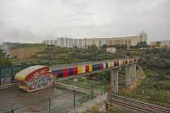 Pista del treno di Colourfull attraverso il terreno incolto urbano con le palazzine di appartamenti Immagini Stock
