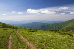 Pista dell'automobile della sporcizia sulla collina erbosa verde che conduce alle montagne legnose cresta sul fondo luminoso dell fotografia stock