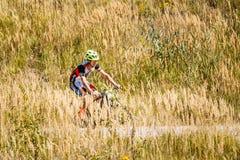 Pista di guida del ciclista del mountain bike in prato con Fotografia Stock