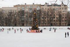Pista di pattinaggio della gente sulla pista di pattinaggio sul ghiaccio pubblica vicino all'albero di Natale sugli stagni patria Fotografia Stock Libera da Diritti