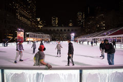 Pista di pattinaggio e pattinatori di pattinaggio su ghiaccio a Bryant Park a New York Fotografia Stock Libera da Diritti
