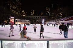Pista e skateres da patinagem no gelo em Bryant Park em New York Fotografia de Stock Royalty Free