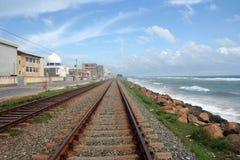 Pista ferroviaria, el cielo azul y el mar azul Fotos de archivo libres de regalías