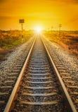 Pista ferroviaria en una escena rural en el tiempo de la puesta del sol Foto de archivo libre de regalías