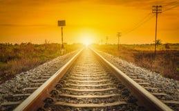 Pista ferroviaria en una escena rural en el tiempo de la puesta del sol Imagen de archivo libre de regalías