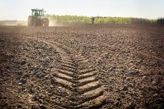 Pista fresca del primo piano distante del trattore sulla terra bagnata della molla Immagini Stock Libere da Diritti