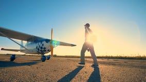 Pista iluminada por el sol con un aviador de sexo masculino que camina hacia un avión y que comprueba su propulsor almacen de metraje de vídeo