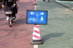 Pista para bicicletas y muestra de la senda para peatones Imagen de archivo libre de regalías