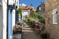 Pista pedestre estreita e casas terraced na vila Robin Hoods Bay foto de stock royalty free
