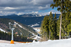 Pista per gli sciatori vicino ad un mazzo di alberi contro il Mountain View dentro Immagini Stock