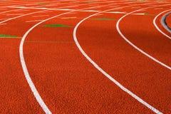 Pista recubierta de goma anaranjada del atletismo Imagen de archivo