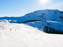 Pista sui pendii della neve delle montagne nel giorno soleggiato Fotografia Stock