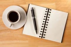 Pista, taza y pluma espirales en blanco de nota en la madera Imágenes de archivo libres de regalías
