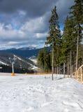 Pista vuota per gli sciatori vicino ad un mazzo di alberi contro la montagna vi Fotografie Stock Libere da Diritti