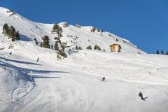 Pista y esquiadores del esquí que esquían cuesta abajo en las montañas Imagen de archivo