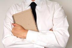 Pista y pluma de nota del asimiento del hombre de negocios Imagenes de archivo