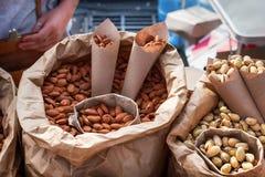 Pistacchi e mandorle salati in un primo piano dei sacchi di carta Alimento della via Fotografie Stock