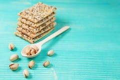 Pistacchi sul cucchiaio e sui biscotti di legno con i semi assortiti sopra fondo d'annata di legno Fotografia Stock Libera da Diritti