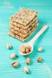 Pistacchi sul cucchiaio e sui biscotti di legno con i semi assortiti sopra fondo d'annata di legno Fotografia Stock