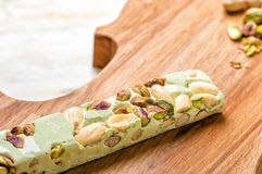 Pistache. A bar of pistachio nougat on a violin shaped wood tray Royalty Free Stock Photos