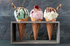 Pistache, cerise et glace à la vanille dans des cônes de gaufre au-dessus d'ardoise Photo libre de droits