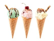 Pistache, cerise et glace à la vanille dans des cônes de gaufre d'isolement sur le blanc Photos stock