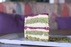 Pistache en bessencake op witte plaat stock afbeelding