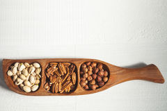 Pistache, noix de pécan et noisettes dans une cuvette en bois Photos stock