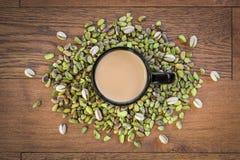 Pistaches délicieuses avec le thé noir chaud de Cardom image stock