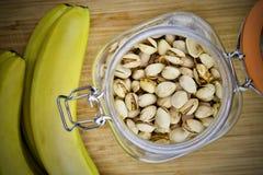 Pistaches dans le pot et les banans jaunes photos libres de droits