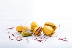 Pistaches dans les coquilles jaunes rôties avec le safran et les épices sèches de safran images stock