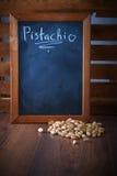 Pistaches dans un scoop sur un plancher en bois brun L'espace noir vide de conseil pour le texte Image stock