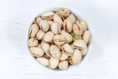 Pistaches de pistaches de panneau en bois de cuvette ci-dessus photos stock
