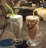 Pistachio and Banana milkshakes. With straws on a table Royalty Free Stock Photography