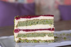 Pistachio and berry cake on white plate stock photo