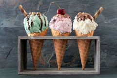 Pistachio, cherry and vanilla ice cream in waffle cones over slate. Pistachio, cherry and vanilla ice cream with topping in waffle cones in rustic wood holder Royalty Free Stock Photo