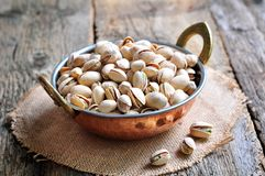 Pistachio in a copper bowl on the old wooden background Royalty Free Stock Photo