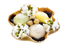Pistachio Hazelnut Cream Ice Cream Waffle Bowl. Waffle bowl filled with pistachio hazelnut cream and chocolate syrup. Ice cream provided and styled by Gelateria Stock Photo