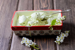 Pistachio ice cream in a big container, bird cherry flowers. On a wooden background Royalty Free Stock Image