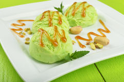 Pistachio ice cream on green wood background Royalty Free Stock Images