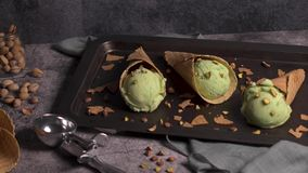 Pistachio ice cream in waffle cones. Balls of pistachio ice cream in waffle cones on a dark background stock video