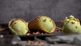 Pistachio ice cream in waffle cones. Balls of pistachio ice cream in waffle cones on a dark background stock video footage