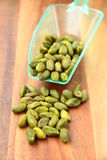 Pistachio nuts. Green pistachio nuts with a yellow spoon  on a wooden background Royalty Free Stock Photography
