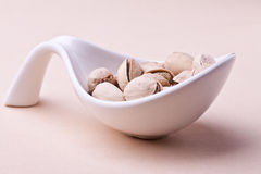 Pistachio nuts. Pistachios in a bowl. closeup on pastel background royalty free stock photography