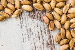 Pistachio Nuts. Aligned on white wooden background with copyspace for text Royalty Free Stock Images