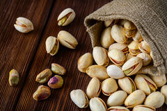 Pistachio nuts in a bag on an old wooden surface Stock Photos