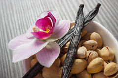 Pistachio nuts, blooming orchid and fragrant vanilla sticks, cosmetic ingredients Stock Photo