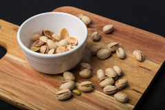 Pistachio Nuts and Empty Shells on Serving Board Stock Photo